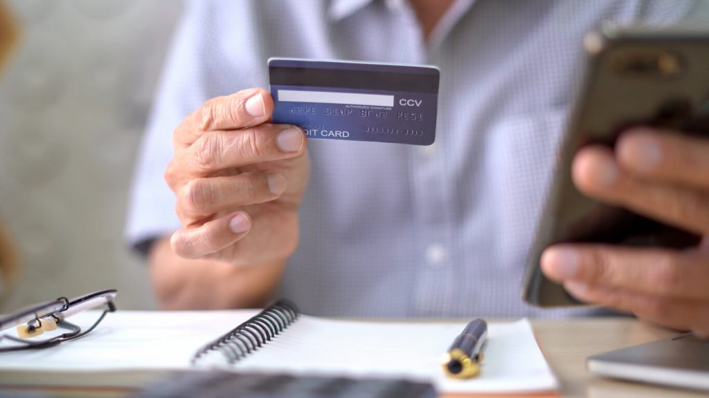 Photo of person with mobile and credit card
